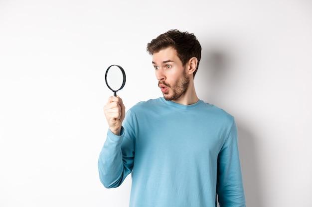 虫眼鏡を通して見ていると、白い背景の上に立って、すごい製品にすごいと言って、男は驚いた。