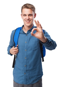 Man grabbing the grips of a blue backpack and saying ok