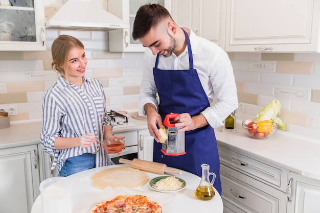 Man grating cheese for pizza with woman
