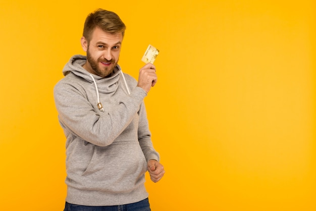 Man in a gray hoodie holding credit card