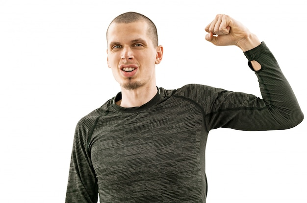 Man in gray run shirt with long sleeves and thump hole feel himself like a winner. hand up of man pumping his fist in the air. runner. sportswear. isolated on a white background. sport