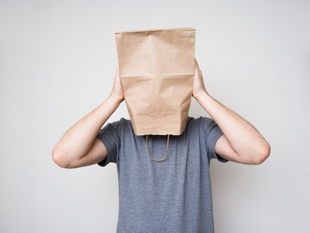 Man in a gray shirt and a paper bag on his head.
