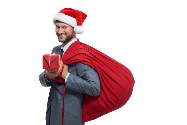 Uomo in suite grigia come babbo natale che dà una scatola con un regalo