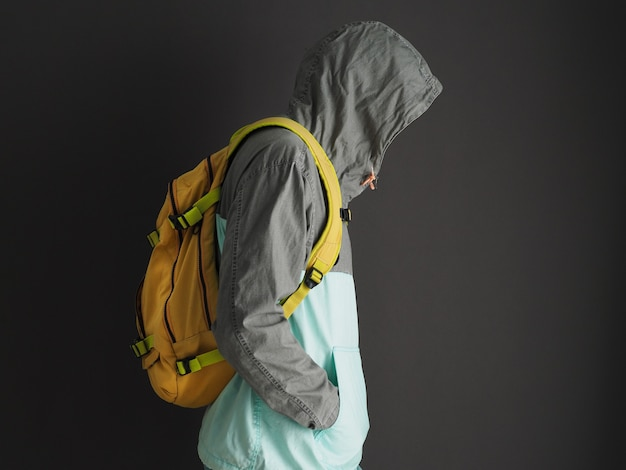 Man in gray sweatshirt hoodie with yellow backpack. profile view.