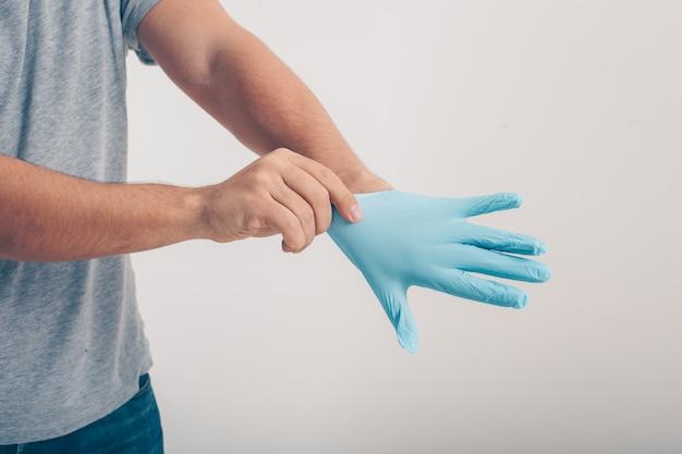 Un uomo in maglietta grigia che indossa i guanti medici nel fondo bianco.
