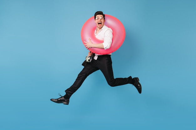 Man in great mood is jumping against blue space with pink rubber ring. portrait of joyful guy in office outfit.