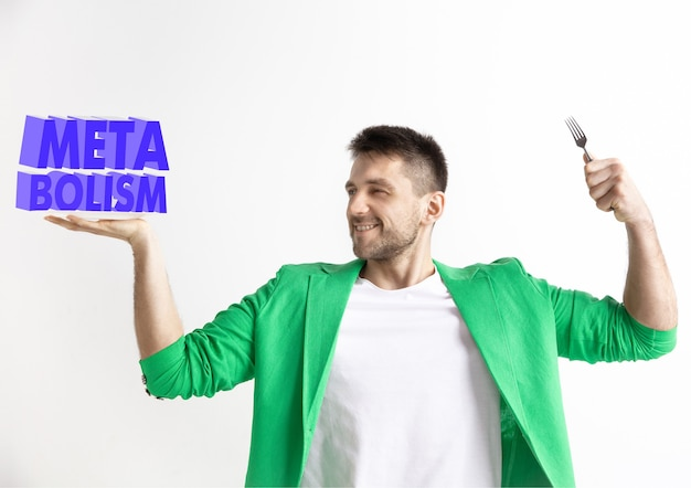 Man in green jacket with the folk isolated on white. male model holding a plate with letters of word metabolism. choosing healthy eating, diet, organic nutrition and nature friendy lifestyle.