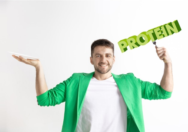 Man in green jacket with the folk isolated on white. male model holding a plate with letters of word protein. choosing healthy eating, diet, organic nutrition and nature friendy lifestyle.