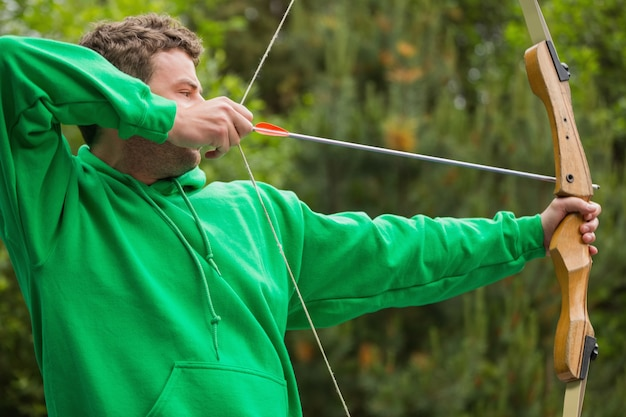 Man in green jumper about to shoot arrow