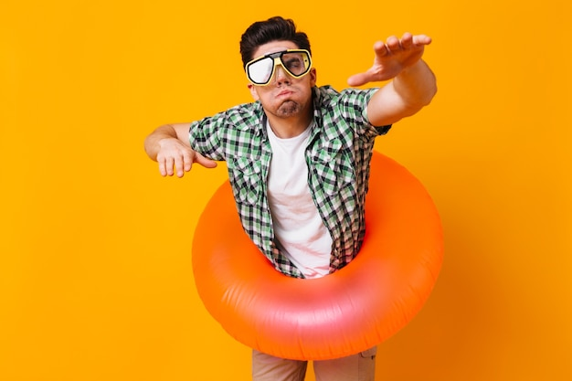 Man in green shirt, diving mask and inflatable circle represents swimming on orange space.