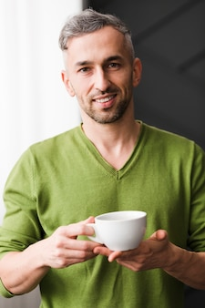 Man in green shirt holding a white cup of coffee