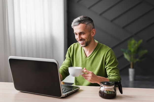 Man in green shirt smiles and using his laptop