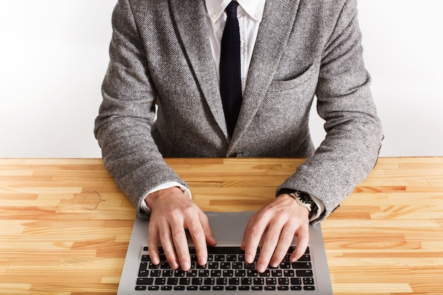 Man in grey office suit types something on the keyboard