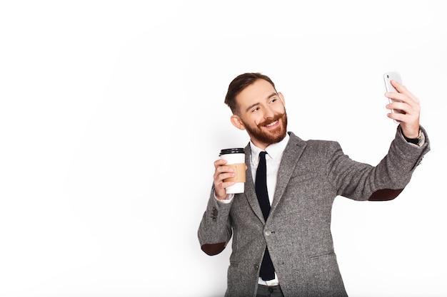 Man in grey suit takes selfie with coffee in her arm