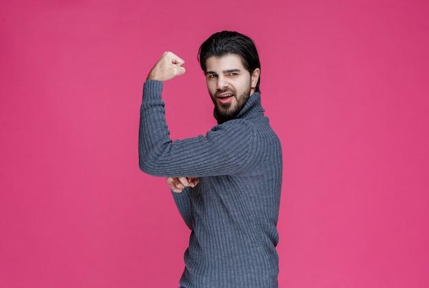 Uomo in maglione grigio che dimostra i suoi muscoli del braccio.