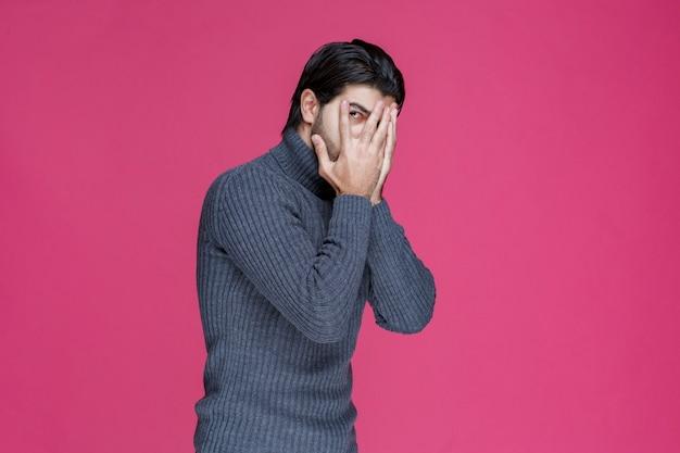 Man in grey sweater looking across his fingers.