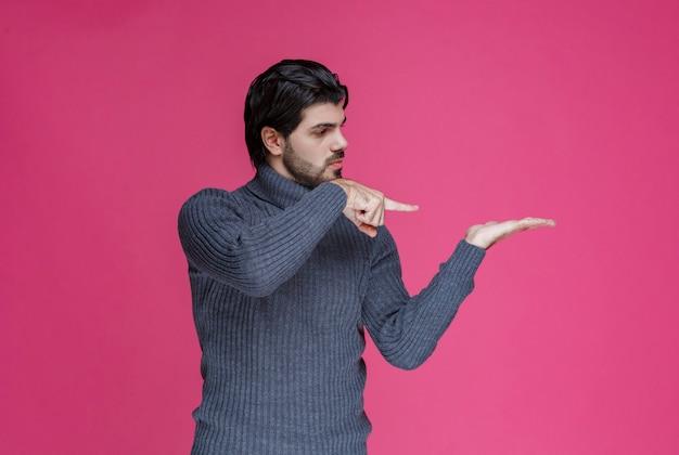 Uomo in maglione grigio che indica la sua mano.