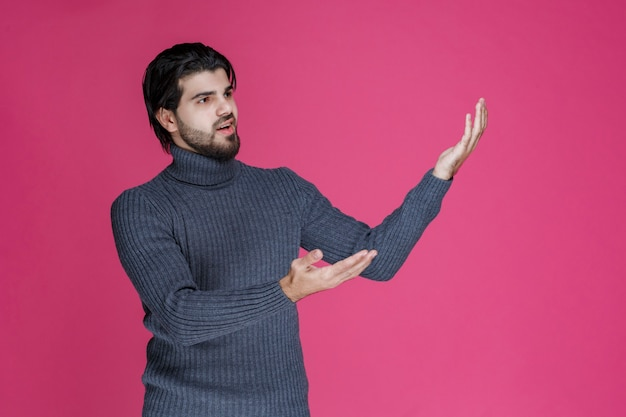 Man in grey sweater pointing and introducing someone.