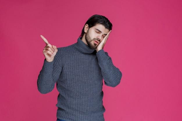 Uomo in maglione grigio che indica e che presenta qualcuno. Foto Gratuite