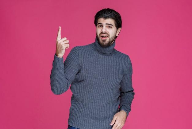 Uomo in maglione grigio per indicare qualcosa o presentare qualcuno usando il dito puntato.