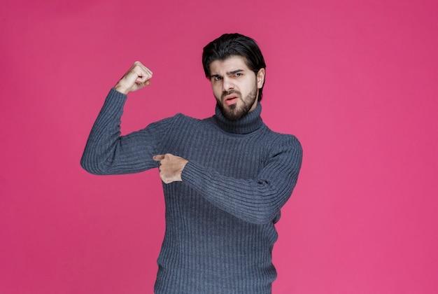 Uomo in maglione grigio che mostra il suo muscolo del braccio.