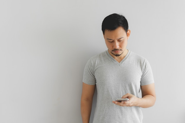Man in grey t-shirt is using the smartphone.