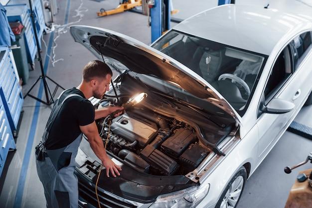 Man in grey uniform repairs white automobile indoors.