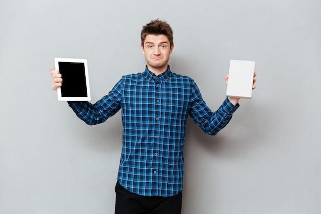 Man over grey wall holding tablet computer and book