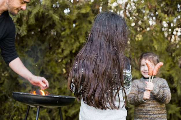 Man grilling outdoors with two daughters