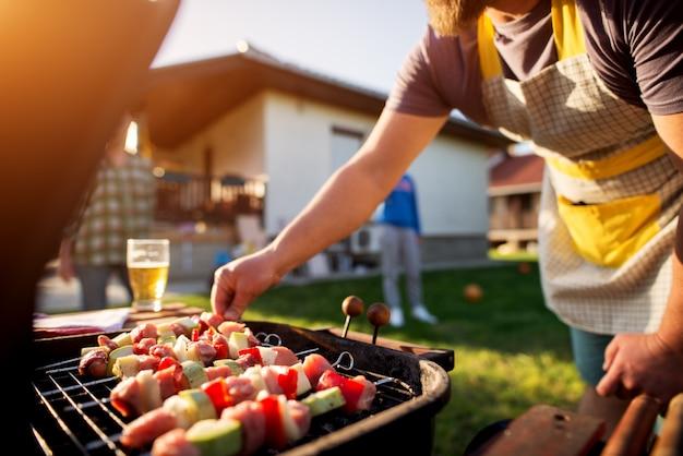 裏庭で野菜を焼く男。