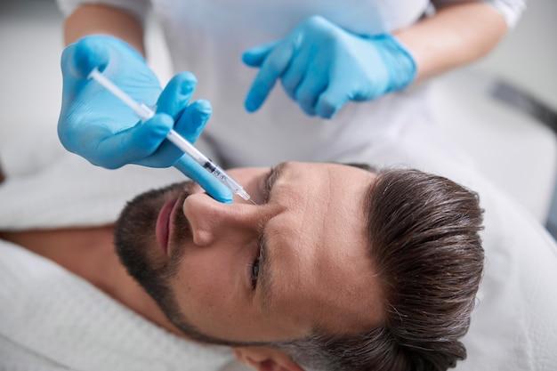 Мужчина морщится от боли, пока опытный косметолог вводит лифтинг-наполнитель в переносицу