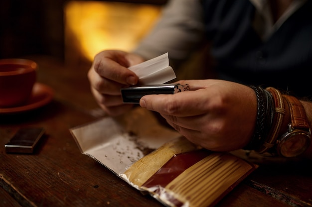 Man grinds tobacco, closeup view, wooden table on background. smoking culture, specific rich flavor. male smoker leisures in office