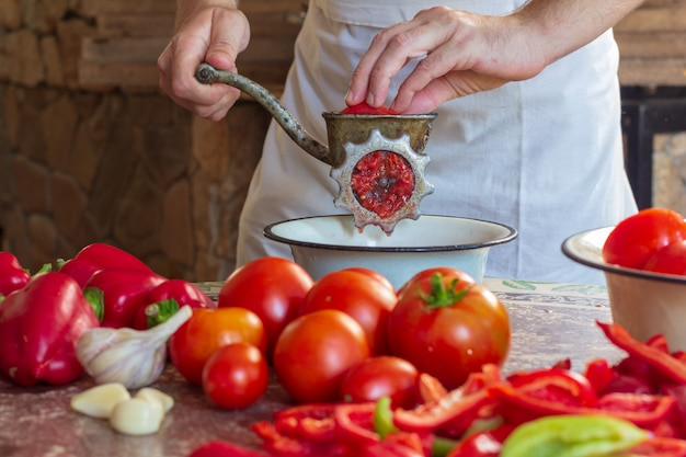 A man grinds tomatoes and bulgarian pepper in a meat grinder to make lecho sauce