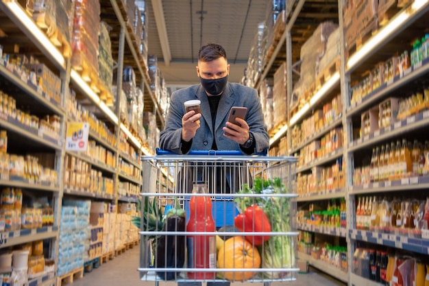 Man in grocery store with cart checking phone copy space