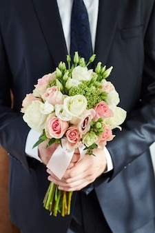 Man groom holds the bridal bouquet. guy in jacket