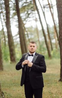 Мужчина жених в стильном костюме позирует