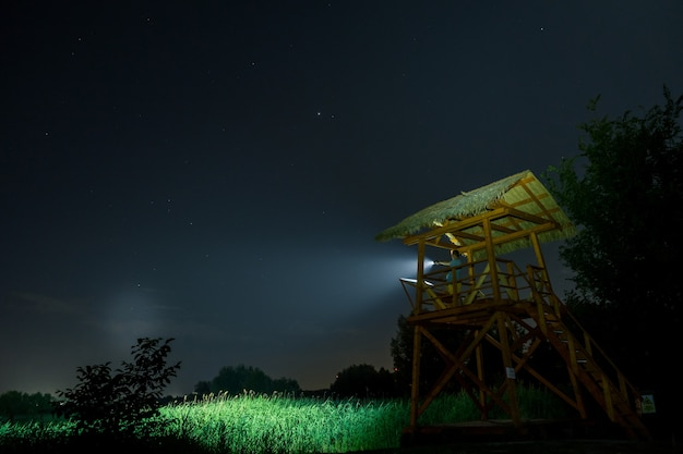 Man guardian in guard post pointing flashlight to field at night.