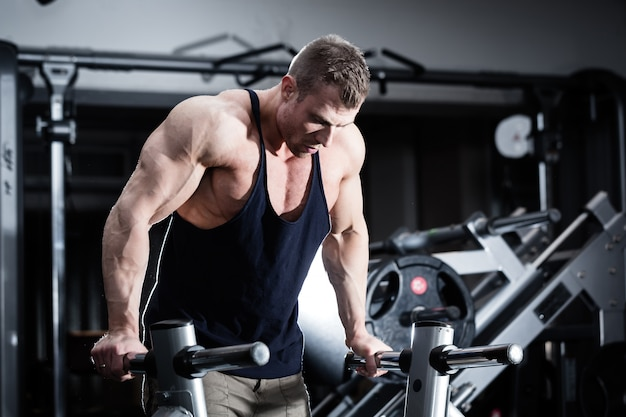 Man in gym at dip exercise