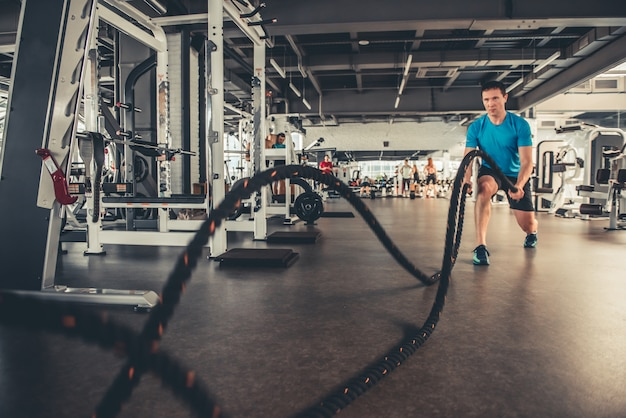 A man in the gym does exercise with a rope.