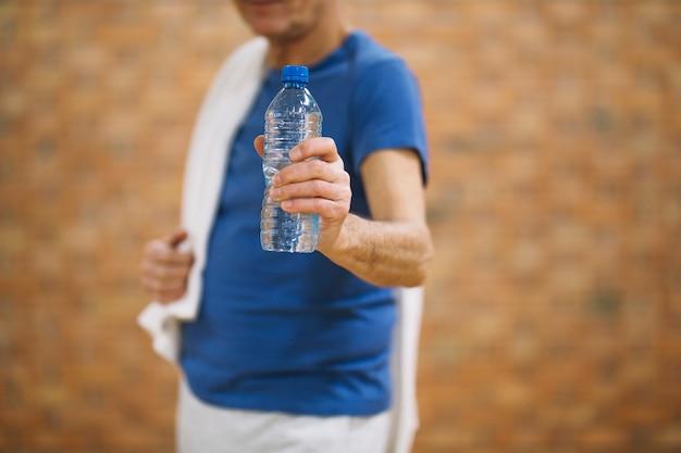 Man in gym showing water bottle