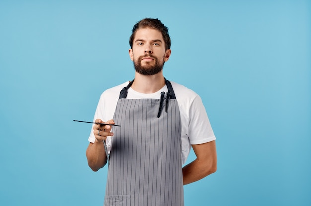 Man hairdresser in gray apron scissors comb barbershop thick beard brunette. high quality photo