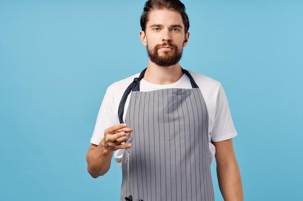 Man hairdresser in gray apron scissors comb barbershop thick beard brunette