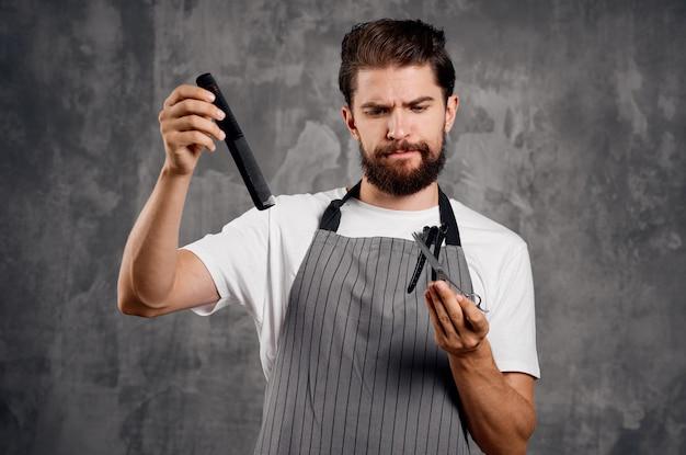 灰色のエプロンのプロの仕事の散髪の男の美容師。高品質の写真