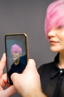 Man hairdressers hands taking picture on smartphone of her client short pink hairstyle