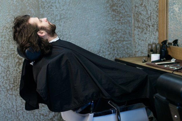 Man at the hairdressing salon sitting in the armchair, waiting for a barber