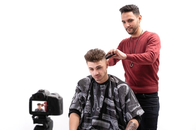 Man hairdressing teacher cutting hair with razor to a client on white background while online classes