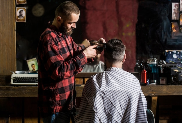 Man hairstylist. hairdresser cutting hair of male client. hairstylist serving client at barber shop.