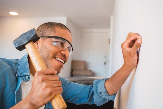 Man hammering nail on the wall
