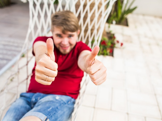 Man in a hammock shows thumb up