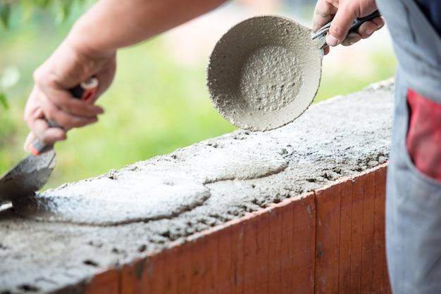 Man hand building wall of bricks